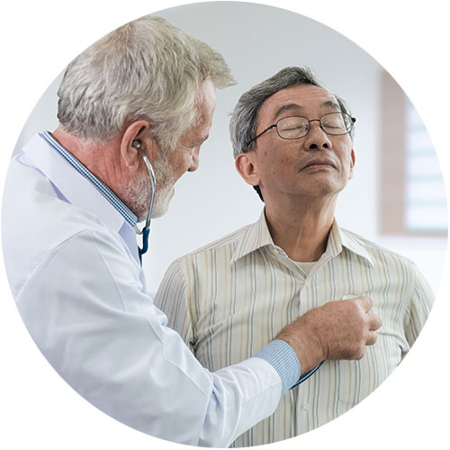 Health care provider uses a stethoscope to listen to the heart of an elderly patient.
