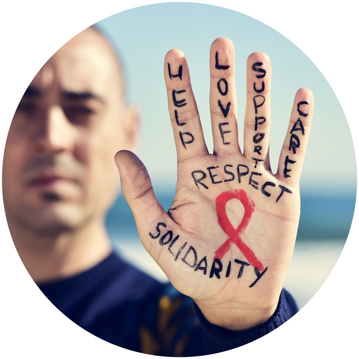 Man shows hand on which a red ribbon and the words Solidarity, Help, Love, Respect, Support and Care are written